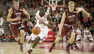 Arkansas guard Fred Gulley III (12) maneuvers down the court alongside South Carolina defenders Mindaugas Kacinas (25) and Brian Steele (35) during the first half of an NCAA college basketball game, Wednesday, Feb. 19, 2014, in Fayetteville, Ark. (AP Photo/Gareth Patterson)