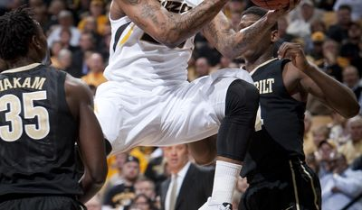 Missouri's Earnest Ross, center, drives toward the basket between Vanderbilt's James Siakam, left, and Dai-Jon Parker, right, during the first half of an NCAA college basketball game, Wednesday, Feb. 19, 2014, in Columbia, Mo. (AP Photo/L.G. Patterson)