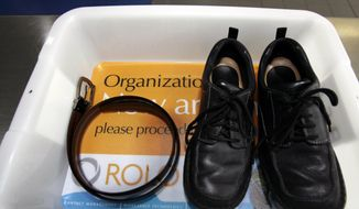 In this Wednesday, Jan. 10, 2007, file photo, a belt and shoes sit in a trays with advertising that is being used in the safety screening of travelers done by the Transportation Security Administration, at the Los Angeles International Airport in Los Angeles. (AP Photo/Ann Johansson, File)