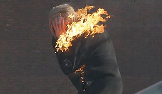 An anti-government protester is engulfed in flames during clashes with riot police outside Ukraine's parliament in Kiev, Ukraine, Tuesday, Feb. 18, 2014. Thousands of angry anti-government protesters clashed with police in a new eruption of violence following new maneuvering by Russia and the European Union to gain influence over this former Soviet republic. (AP Photo/Efrem Lukatsky)