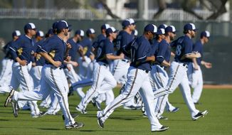 Milwaukee Brewers pitchers run sprints during spring training baseball practice, Monday, Feb. 17, 2014, in Phoenix. (AP Photo/Ross D. Franklin)
