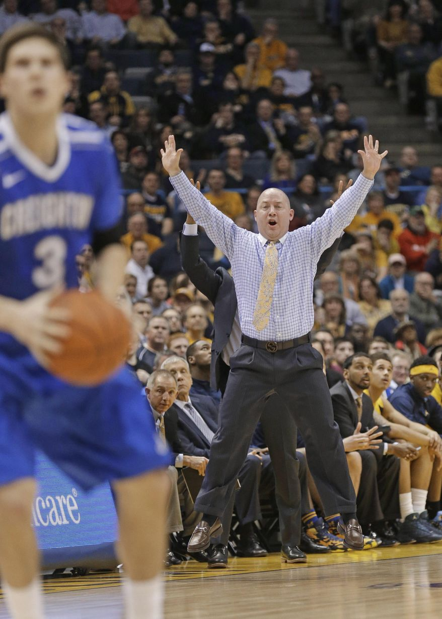 Marquette coach Buzz Williams leaps in the air as he shouts instructions during the second half of an NCAA college basketball game against Creighton on Wednesday, Feb. 19, 2014, in Milwaukee. At left is Creighton's Doug McDermott. Creighton won 85-70.  (AP Photo/Jeffrey Phelps)