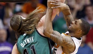 Phoenix Suns' Marcus Morris (15) is fouled by Boston Celtics' Kelly Olynyk (41) during the first half of an NBA basketball game, Wednesday, Feb. 19, 2014, in Phoenix. (AP Photo/Ross D. Franklin)