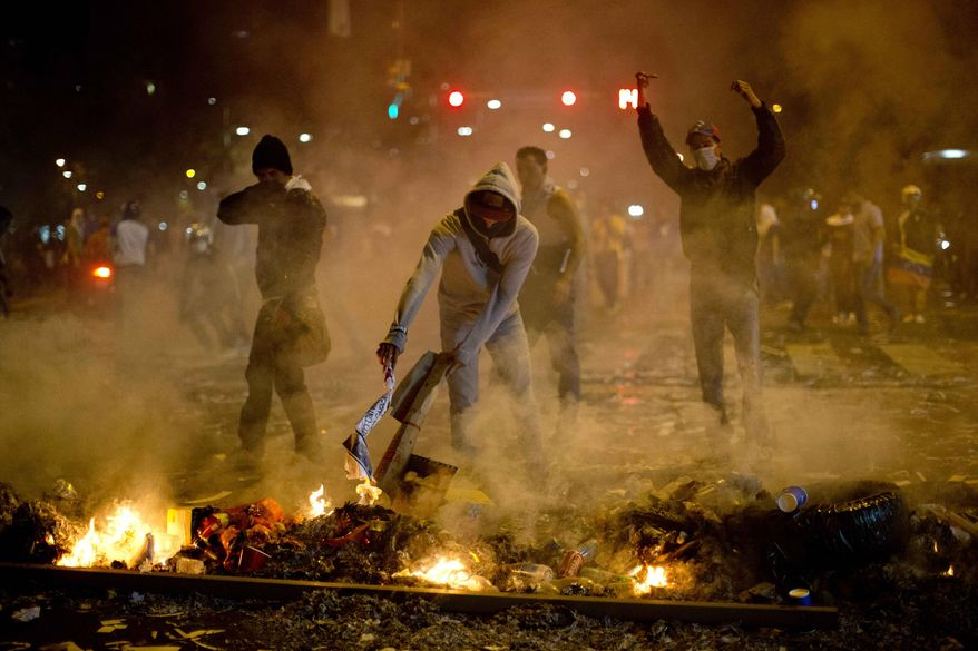 Demonstrators block a street with a burning barricade in the Altamira neighborhood of Caracas, Venezuela, Wednesday, Feb. 19, 2014. Venezuelan security forces backed by water tanks and tear gas dispersed groups of anti-government demonstrators who tried to block Caracas' main highway Wednesday evening. (AP Photo/Rodrigo Abd)