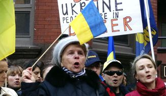 Maria Semkiv, 66, gathers with others outside the Ukrainian embassy in Chicago, Wednesday, Feb. 19, 2014, to protest the deadly violence in the Ukraine capital of Kiev and call for a stronger response by the United States and the European Union. Clashes on Tuesday left 25 people dead in the worst violence in nearly three months of anti-government protests in Ukraine's capital. Protests began after the president backed away from a deal to join the European Union. (AP Photo/Tammy Webber)