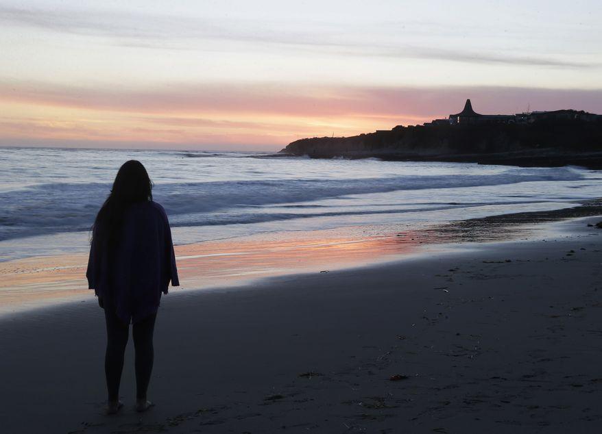 ** FILE ** Shalom Medina, a student at the University of California, Santa Cruz, watches the sunset from the beach at Natural Bridges State Beach on Wednesday, Feb. 19, 2014, in Santa Cruz, Calif. (AP Photo/Marcio Jose Sanchez)