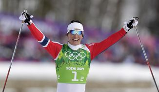 Norway's Marit Bjoergen celebrates winning the gold during the women's cross-country team sprint competitions at the 2014 Winter Olympics, Wednesday, Feb. 19, 2014, in Krasnaya Polyana, Russia. (AP Photo/Matthias Schrader)