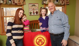 In this Jan. 28, 2014 photo, from left, Gabrielle, Greyson, Emerson and Frank Shimkus wait for the fifth member of their family, Aidan, who is in an orphanage in Kyrgyzstan, in Aidan's bedroom in their Throop, Pa., home. The bedroom decorated for Aidan includes flags and other decorations from his native country. (AP Photo/Scranton Times & Tribune, Jake Danna Stevens)  WILKES BARRE TIMES-LEADER OUT; MANDATORY CREDIT