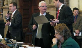 Kansas state Senator's Garrett Love, right and Pat Apple, center, talk as Sen. Dennis Pyle, left, questions a bill expanding the state's no call law for telephone solicitors, Wednesday, Feb. 19, 2014, in Topeka, Kan. The Senate advanced the bill. (AP Photo/John Hanna)