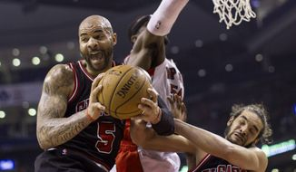 Chicago Bulls' Carlos Boozer (5) claims a rebound in front of Toronto Raptors' Patrick Patterson and Bulls' Joakim Noah during the first half of an NBA basketball game, Wednesday, Feb. 19, 2014 in Toronto. (AP Photo/The Canadian Press, Chris Young)