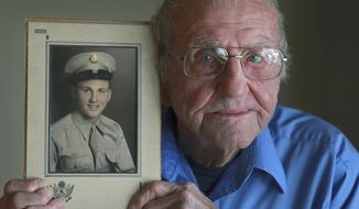 ADVANCE FOR USE SATURDAY, FEB. 22 AND THEREAFTER - In this Jan. 31, 2014, 2014 photo, World War II veteran Lynold Puterbaugh holds a portrait of him in his Army uniform that was taken in 1944 at his home in Pleasant Hill, Ill. (AP Photo/The Quincy Herald-Whig, Phil Carlson)