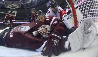 Latvia defenseman Kristaps Sotnieks  reaches over Latvia goaltender Kristers Gudlevskis to grab the puck and keep it from completely crossing the goal line during the third period of a men's ice hockey game against Canada at the 2014 Winter Olympics, Wednesday, Feb. 19, 2014, in Sochi, Russia. The goal was disallowed and ruled dead. Canada won 2-1. (AP Photo/Bruce Bennett, Pool)