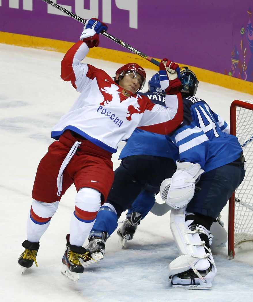 Russia forward Alexander Ovechkin, left, loses his balance while trying to score against Finland in the second period of a men's quarterfinal ice hockey game at the 2014 Winter Olympics, Wednesday, Feb. 19, 2014, in Sochi, Russia. (AP Photo/Mark Humphrey)