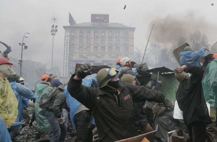Anti-government protesters throw stones during clashes with riot police in Kiev's Independence Square, the epicenter of the country's current unrest, Kiev, Ukraine, Wednesday, Feb. 19, 2014. The deadly clashes in Ukraine's capital have drawn sharp reactions from Washington, generated talk of possible European Union sanctions and led to a Kremlin statement blaming Europe and the West. (AP Photo/Efrem Lukatsky)