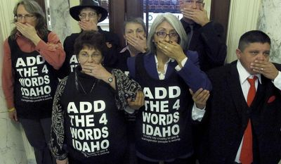 More than two dozen protesters seeking to convince Idaho lawmakers to add discrimination protections for gays and lesbians to the state's Human Rights Act block two entrances to the Idaho Senate in Boise on Thursday, Feb. 20, 2014. At a similar protest on Feb. 3, 44 demonstrators were arrested and charged with misdemeanor tresspassing. (AP Photo/John Miller)