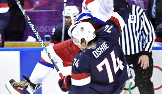 United States forward  T.J. Oshie (74) is hit by Russia forward Alex Ovechkin, back, during a men's ice hockey game at the 2014 Winter Olympics, Saturday, Feb. 15, 2014, in Sochi, Russia. The U.S. won 3-2 in a shootout. (AP Photo/The Canadian Press, Nathan Denette)