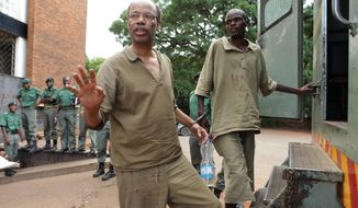** FILE ** Former U.S. Rep. Mel Reynolds, center left, prepares to enter a prison truck while handcuffed  following his court appearance at the magistrates courts in Harare, Thursday, Feb.  20, 2014. (AP Photo/Tsvangirayi Mukwazhi)