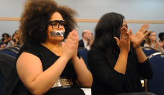 University of Michigan alumna, Asia Blaney, and business school senior, Shayla Scales, clap after listening to a graduate student discuss his experiences as a black student at the university during a Board of Regents meeting Thursday, February 20 at the Michigan Union in Ann Arbor, Mich. (AP Photo/The Ann Arbor News, Brianne Bowen)