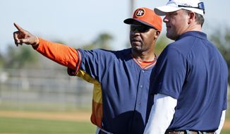 Houston Astros manager Bo Porter, left, talks with former pitcher Roger Clemens during a spring training baseball workout, Wednesday, Feb. 19, 2014, in Kissimmee, Fla. (AP Photo/Alex Brandon)