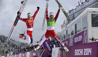 Norway's Ingvild Flugstad Oestberg, left, and Marit Bjoergen celebrate winning the gold after the women's cross-country team sprint competitions at the 2014 Winter Olympics, Wednesday, Feb. 19, 2014, in Krasnaya Polyana, Russia. (AP Photo/Matthias Schrader)
