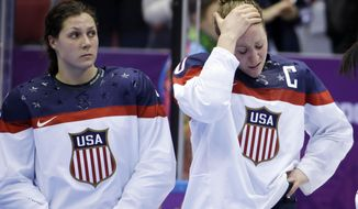 Meghan Duggan of the United States (10), right, reacts after Canada won 3-2 in overtime of the gold medal women's ice hockey game at the 2014 Winter Olympics, Wednesday, Feb. 19, 2014, in Sochi, Russia. (AP Photo/David Goldman)