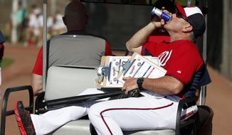 Washington Nationals hitting coach Rick Schu drinks a RedBull as he arrives for a spring training baseball workout, Thursday, Feb. 20, 2014, in VIera, Fla. (AP Photo/Alex Brandon) ** FILE **