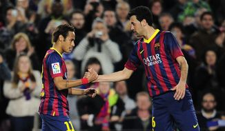 FC Barcelona's Neymar, from Brazil, is congratulated by his teammate Sergio Busquets after scoring against Rayo Vallecano during a Spanish La Liga soccer match at the Camp Nou stadium in Barcelona, Spain, Saturday, Feb. 15, 2014. (AP Photo/Manu Fernandez)