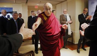"Tibetan spiritual leader the Dalai Lama greets audience members as he arrives to speak at an event entitled: ""Happiness, Free Enterprise, and Human Flourishing"" Thursday, Feb. 20, 2014, at the American Enterprise Institute in Washington. (AP Photo/Charles Dharapak)"