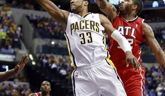 Indiana Pacers forward Danny Granger (33) puts up a shot while guarded by Atlanta Hawks forward Mike Scott during the second half of an NBA basketball game in Indianapolis, Tuesday, Feb. 18, 2014. (AP Photo/R Brent Smith)