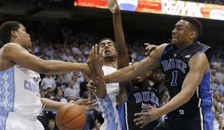 North Carolina's Kennedy Meeks, left, and James Michael McAdoo struggle for possession of the ball with Duke's Amile Jefferson and Jabari Parker (1) during the first half of an NCAA college basketball game in Chapel Hill, N.C., Thursday, Feb. 20, 2014. (AP Photo/Gerry Broome)