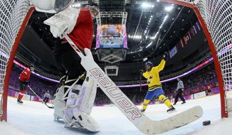 Goalkeeper Florence Schelling of Switzerland takes the puck out of the net after Michelle Lowenhielm of Sweden, not shown, during the women's bronze medal ice hockey game at the 2014 Winter Olympics, Thursday, Feb. 20, 2014, in Sochi, Russia. (AP Photo/Martin Rose, Pool)