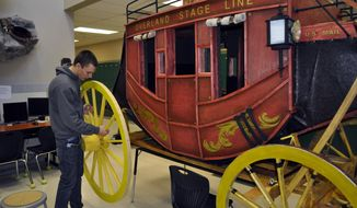 In this Feb. 4, 2014 photo, Powell High School art student Austin Ouellette places a wheel on a replica of the Concord stagecoach created by art students, in Powell, Wyo. Once finished, the stagecoach will be on display in the Powell High School library. (AP Photo/The Powell Tribune, Tessa Schweigert)