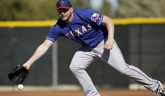 Texas Rangers' Matt Harrison attempts to reach a ground ball on the mound during fielding drills at spring training baseball practice, Monday, Feb. 17, 2014, in Surprise, Ariz. (AP Photo/Tony Gutierrez)