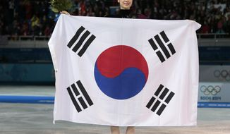 Yuna Kim of South Korea poses with the national flag as she celebrates her second place for the women's free skate figure skating final at the Iceberg Skating Palace during the 2014 Winter Olympics, Thursday, Feb. 20, 2014, in Sochi, Russia. Sotnikova placed first, followed by Kim and Kostner. (AP Photo/Ivan Sekretarev)