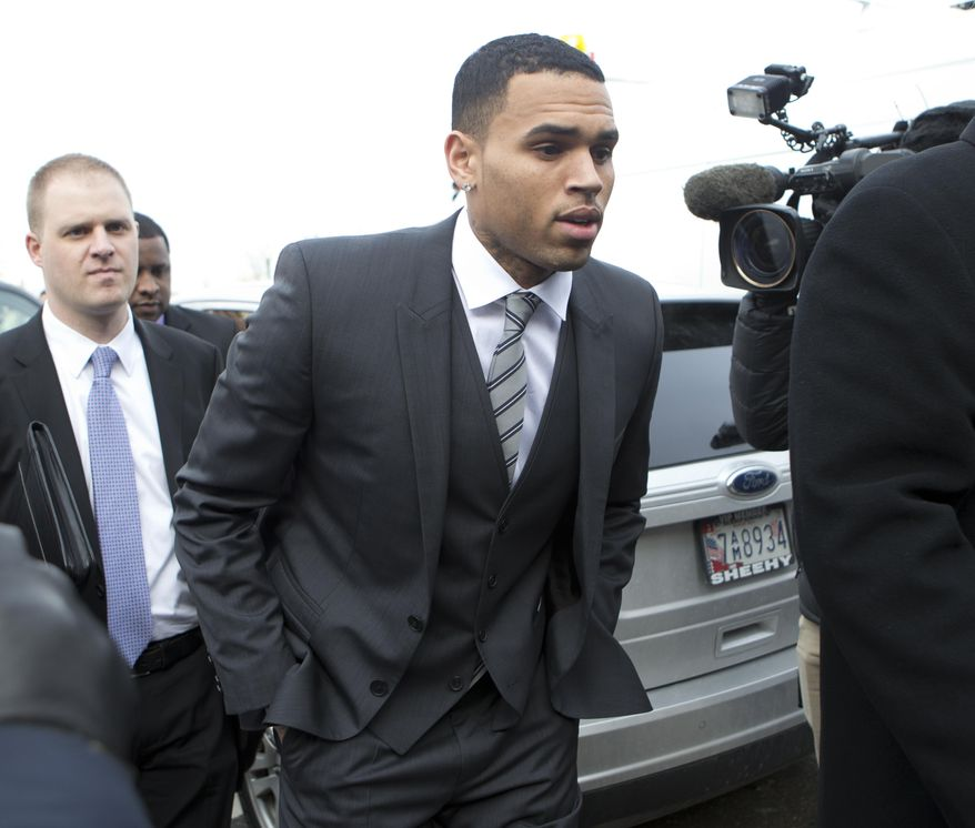 FILE - In this Wednesday, Jan. 8, 2014 file photo, singer Chris Brown, right, arrives at the District of Columbia Superior Court in Washington, for a status hearing in a case in which he's accused of hitting a man outside a Washington hotel. Lawyers for Brown are due back in a Washington court Thursday Feb. 20, 2014 to determine a date for his trial on a misdemeanor assault charge, but the singer won't be in town.  (AP Photo/Manuel Balce Ceneta, File)