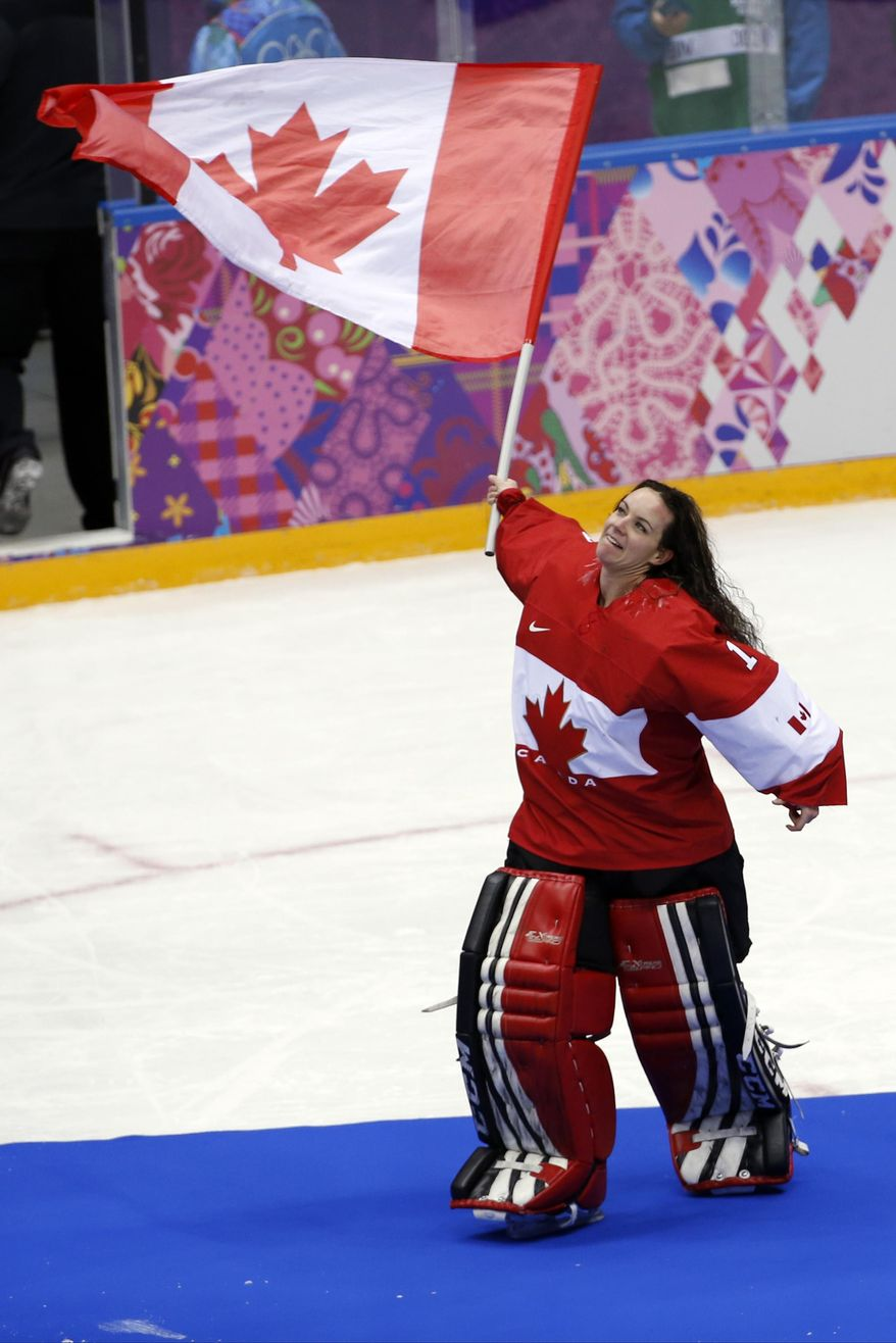 Goalkeeper Shannon Szabados of Canada (1) wave a flag after  the women's gold medal ice hockey game against USA at the 2014 Winter Olympics, Thursday, Feb. 20, 2014, in Sochi, Russia. (AP Photo/Petr David Josek)