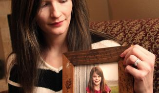 Erin Petersen holds a photo of her niece, Hailey Owens, Wednesday Feb. 19, 2014. A middle-school football coach has been jailed on suspicion of first-degree murder in the abduction and death of a 10-year-old girl in southwest Missouri, police said Wednesday. (AP Photo/The Springfield News-Leader, Christine Temple)