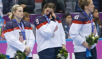 Megan Bozek of the United States (9) wipes a tear as she stand with Monique Lamoureux of the United States (7),  and Meghan Duggan of the United States (10) during the medal ceremony for the women's ice hockey tournament at the 2014 Winter Olympics, Friday, Feb. 21, 2014, in Sochi, Russia. Team USA took silver after losing 3-2 to Team Canada in overtime. (AP Photo/Matt Slocum)