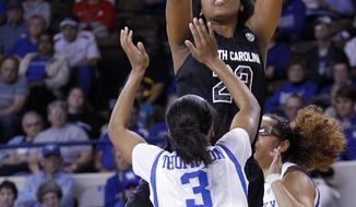 South Carolina's Tina Roy, top, shots between Kentucky's Janee Thompson (3) and Jennifer O'Neill during the first half of an NCAA college basketball game, Thursday, Feb. 20, 2014, in Lexington, Ky. (AP Photo/James Crisp)