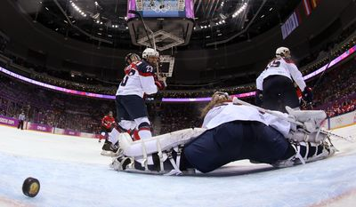 The puck gets past USA Goalkeeper Jessie Vetter (31) for the game-winning goal against Canada in the women's gold medal ice hockey game at the 2014 Winter Olympics, Thursday, Feb. 20, 2014, in Sochi, Russia. (AP Photo/Martin Rose, Pool)