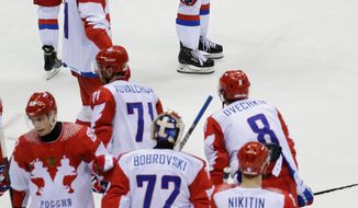 Members of Team Russia stand on the ice after their 3-1 loss to Finland in the men's quarterfinal hockey game in Bolshoy Arena at the 2014 Winter Olympics, Wednesday, Feb. 19, 2014, in Sochi, Russia. (AP Photo/David J. Phillip )