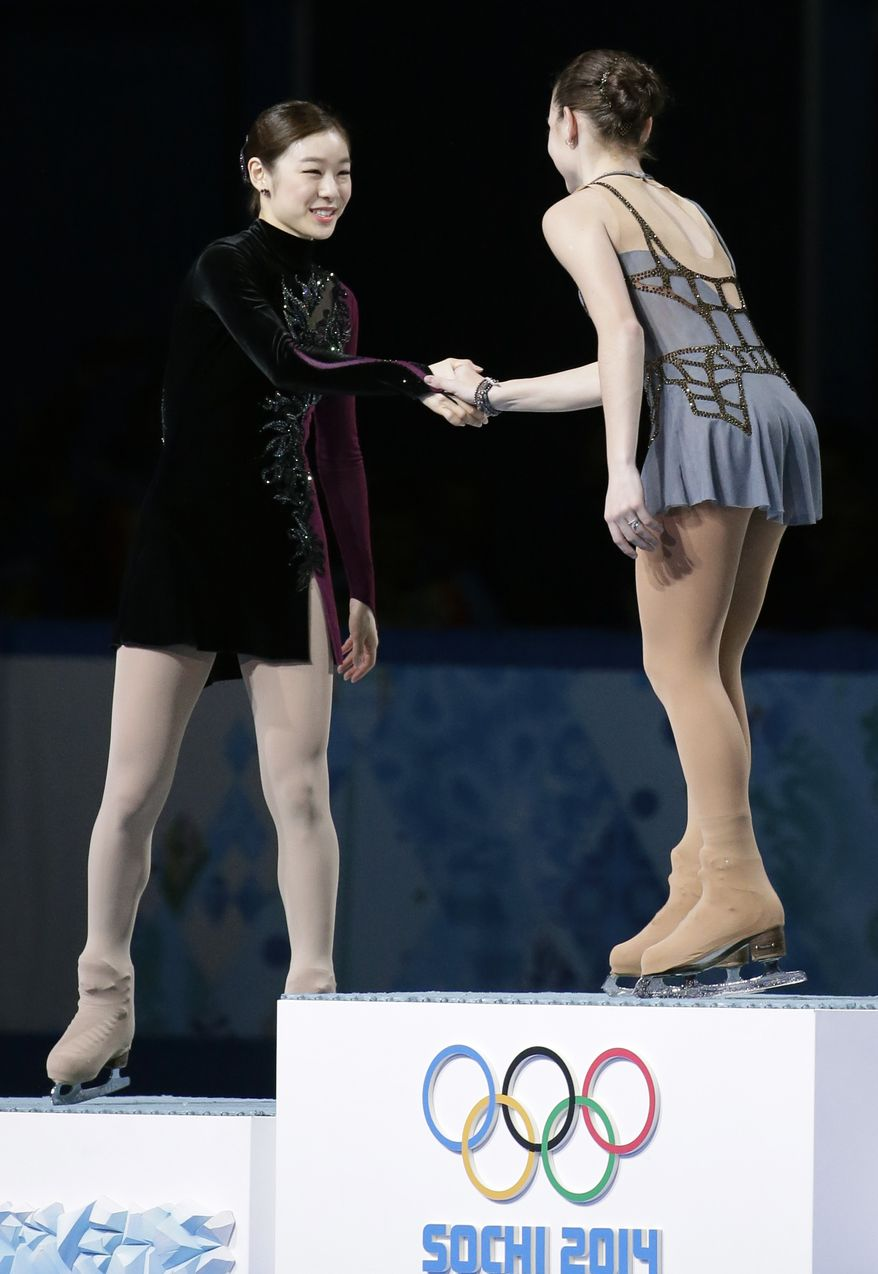 Yuna Kim of South Korea, left, shakes hands with Adelina Sotnikova of Russia as they stand on the podium during the flower ceremony for the women's free skate figure skating finals at the Iceberg Skating Palace during the 2014 Winter Olympics, Thursday, Feb. 20, 2014, in Sochi, Russia. Sotnikova placed first, followed by Kim and Kostner. (AP Photo/Bernat Armangue)