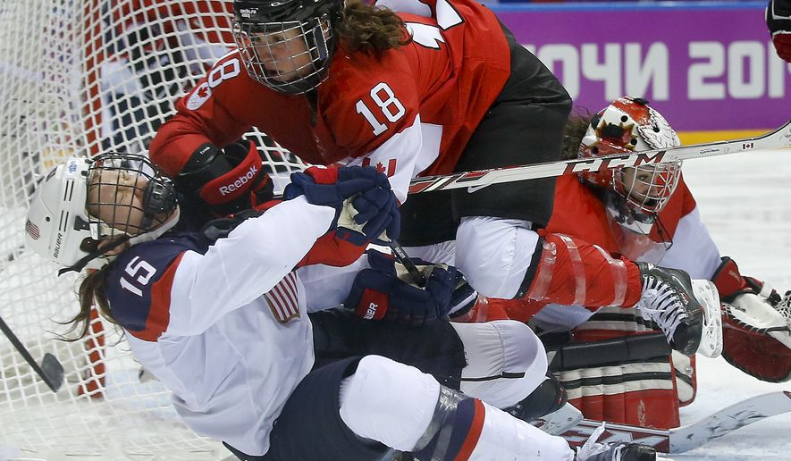 Catherine Ward of Canada (18) shoves Anne Schleper of the United States (15) to the ice during overtime of the women's gold medal ice hockey game at the 2014 Winter Olympics, Thursday, Feb. 20, 2014, in Sochi, Russia. (AP Photo/Matt Slocum)
