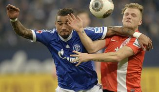 Schalke's Kevin-Prince Boateng of Ghana, left, and Mainz's Johannes Geis challenge for the ball during the German Bundesliga soccer match between FC Schalke 04 and FSV Mainz 05 in Gelsenkirchen,  Germany, Friday, Feb. 21, 2014. (AP Photo/Martin Meissner)