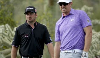 Graeme McDowell, of Northern Ireland, left, and Hunter Mahan look down the 17th hole during the third round of the Match Play Championship golf tournament on Friday, Feb. 21, 2014, in Marana, Ariz. (AP Photo/Ted S. Warren)