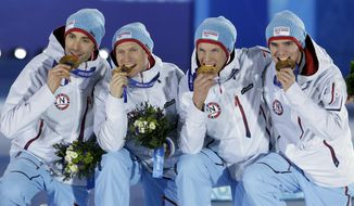 The team from Norway, who won the gold medal in the team Gundersen large hill Nordic combined competition, bite their medals at the 2014 Winter Olympics, Thursday, Feb. 20, 2014, in Sochi, Russia. (AP Photo/Morry Gash)