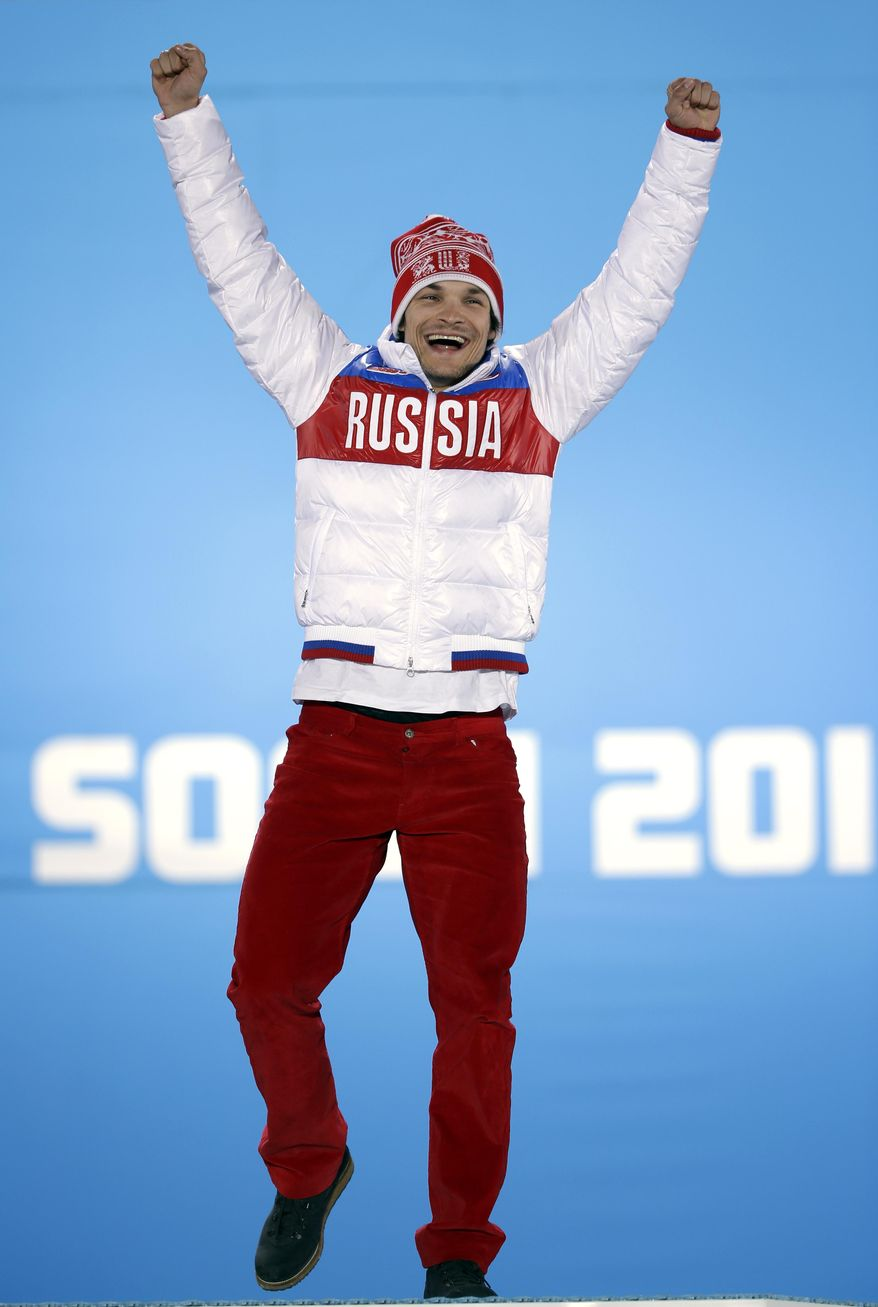 Vic Wild of Russia, the gold medalist in the men's snowboard parallel giant slalom, celebrates during the medals ceremony at the 2014 Winter Olympics, Wednesday, Feb. 19, 2014, in Sochi, Russia. (AP Photo/David Goldman)