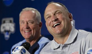 FILE - In this June 14, 2013, file photo, North Carolina State coach Elliott Avent, right, laughs with North Carolina coach Mike Fox during a news conference in Omaha, Neb. The programs separated by about a 30-minute drive enter the 2014 season among the nation's top-ranked teams--and they'd love to have another rendezvous on the sport's biggest stage. (AP Photo/Nati Harnik, File)