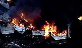 In this image from video from KOMO News, multiple boats burn at the Shelter Bay Marina near La Conner, Wash., sending up a huge cloud of black smoke, on Friday, Feb. 21, 2014. Fire crews poured water on the blazing boats from land and from a fireboat. There were no immediate reports of injuries. (AP Photo/KOMO-TV) SEATTLE OUT
