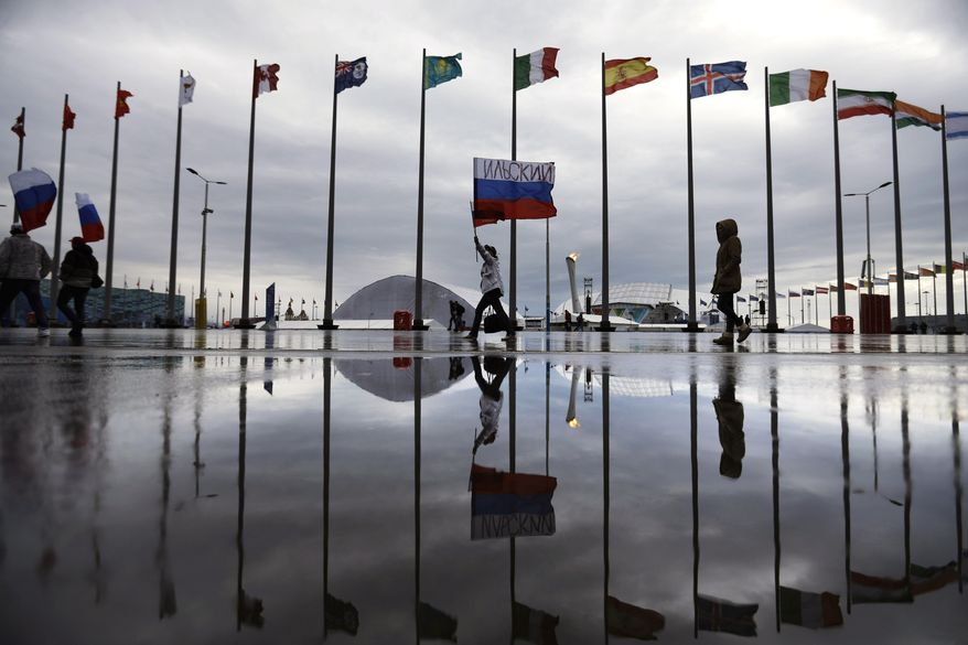 A fan is reflected in a puddle carrying the Russian flag past the Olympic cauldron at the 2014 Winter Olympics, Tuesday, Feb. 18, 2014, in Sochi, Russia. (AP Photo/David Goldman)